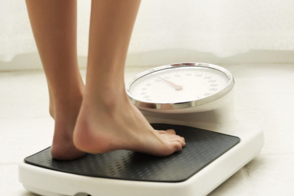 Young fit woman stepping on a bathroom scale. Square shot.