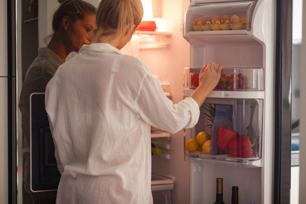 Young woman standing beside open refrigerator at home in the morning