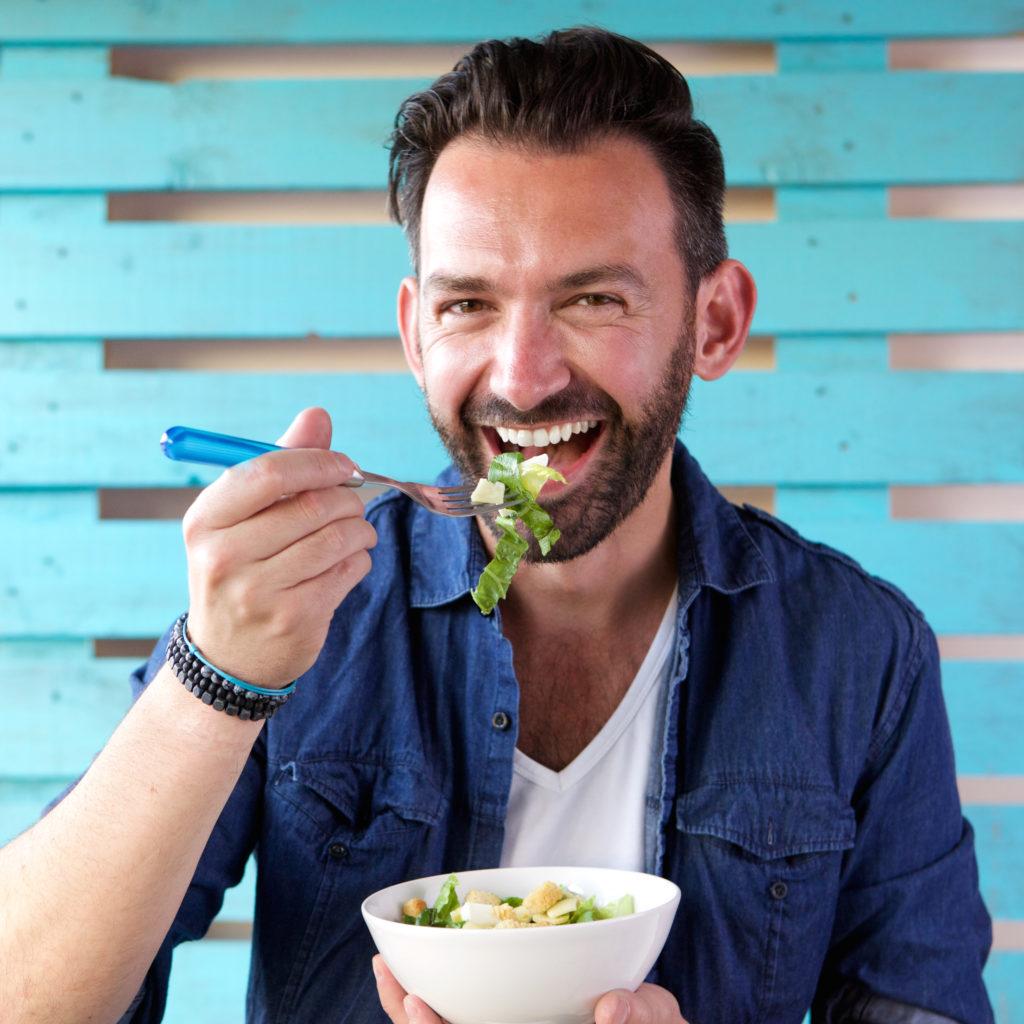 Portrait of cheerful man eating salad