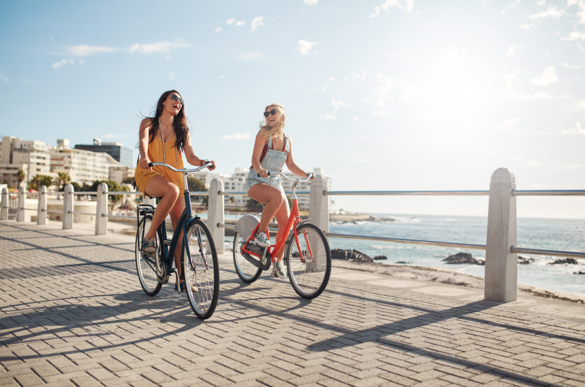 Two young female friends riding their bicycles on the seaside promenade. Cheerful young women riding bikes at the waterfront on a summer day.
