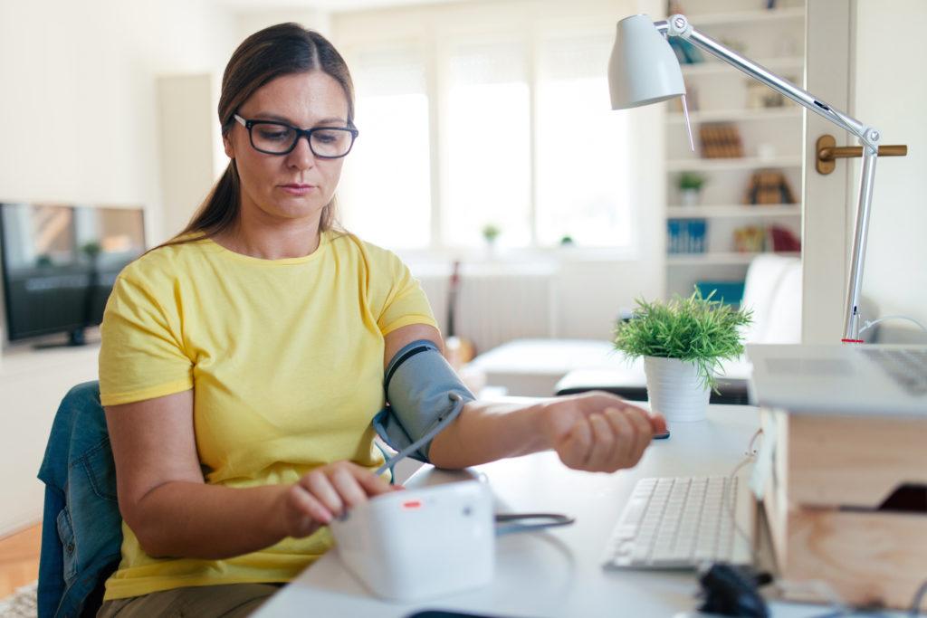Photo of woman checking blood presure at home