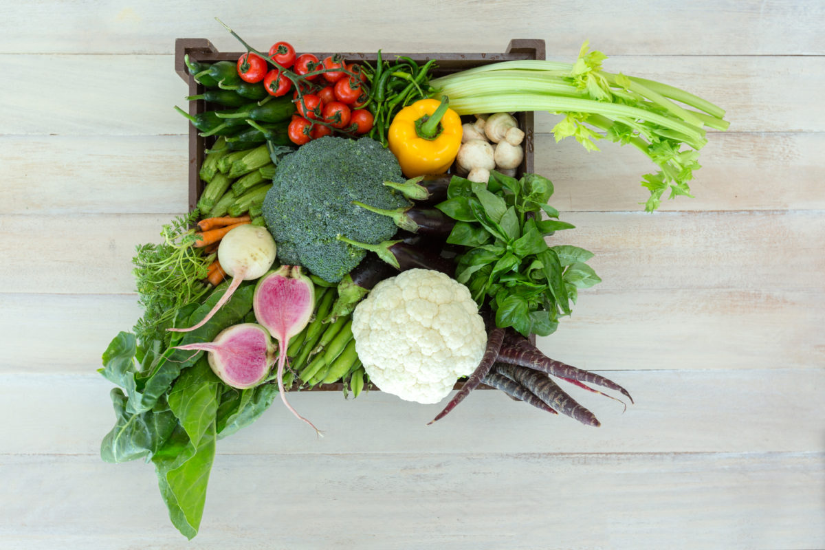Old wooden crate packed full with fresh vegetables.