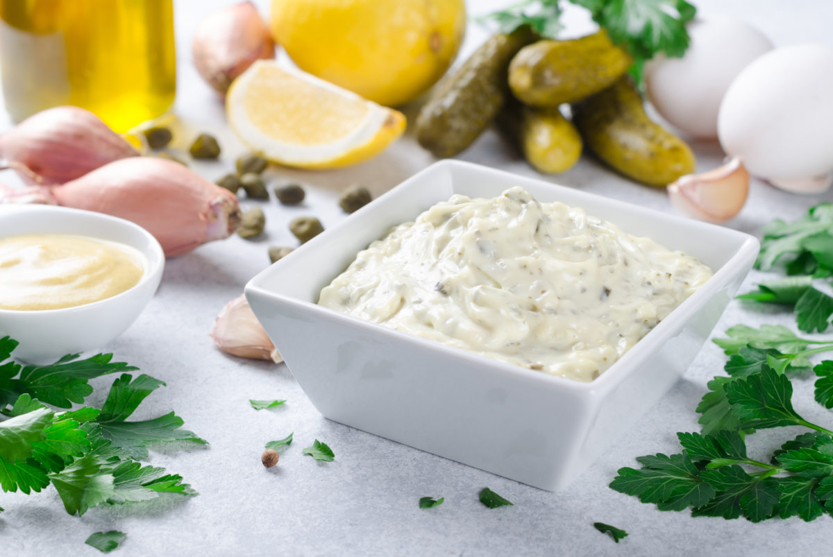 Homemade traditional french sauce remoulade in a white bowl with ingredients, lemon, eggs, shallot onion, pickles, parsley, mustard on a light stone background. Horizontal