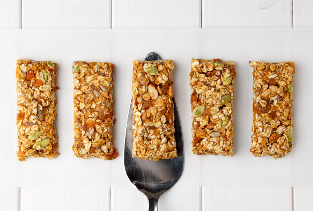 No bake energy granola bars on white wooden table with spatula. Top view.