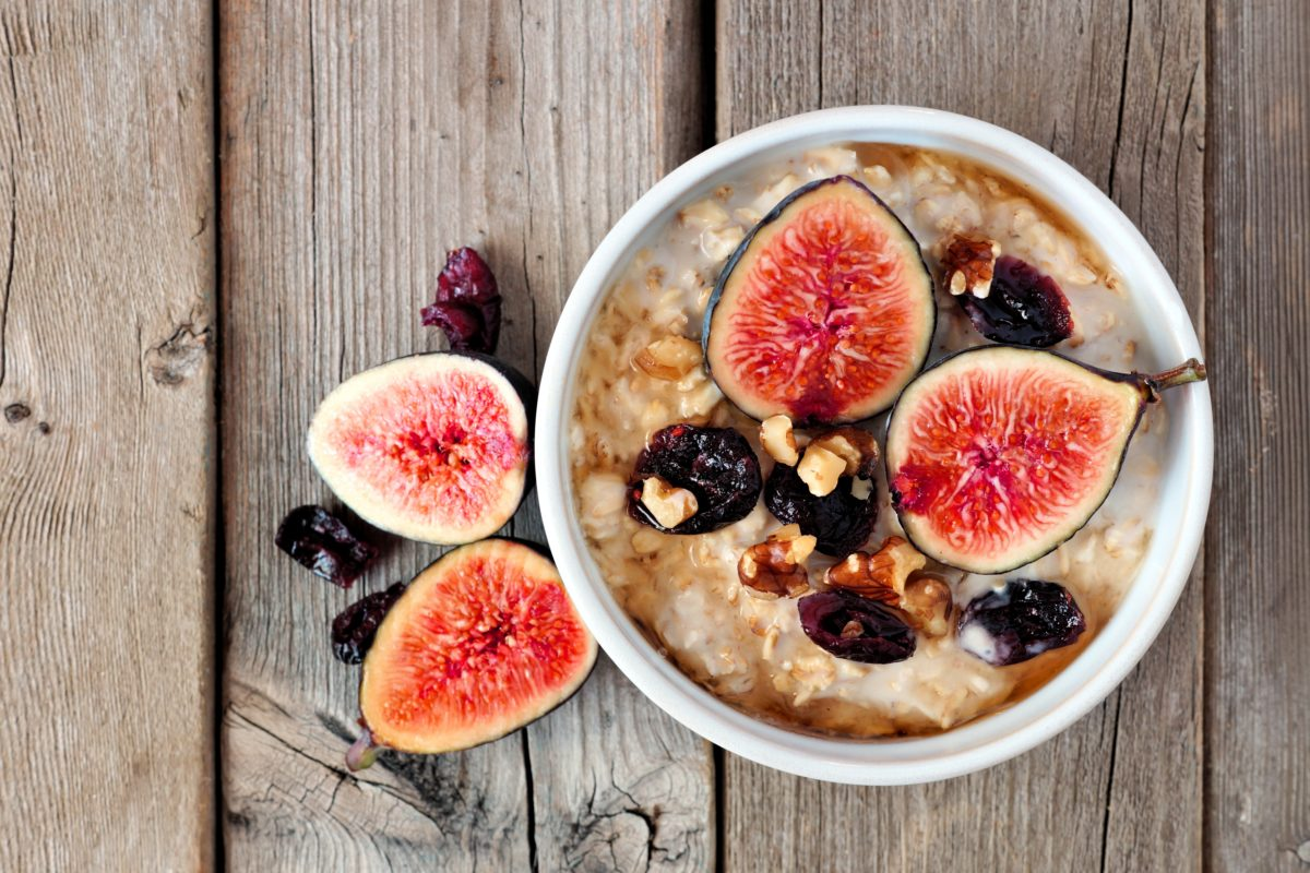 Oatmeal with red figs, cranberries and walnuts in a bowl, above view on rustic wood