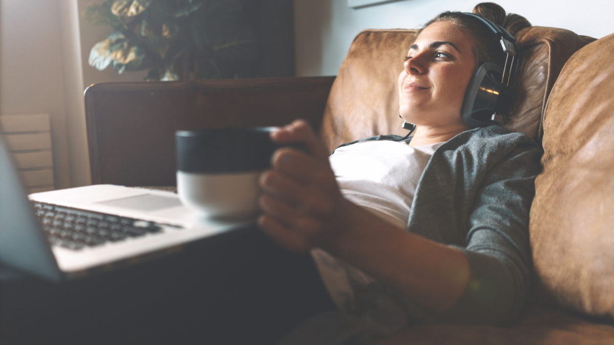 Pretty smiling girl listening to music from headphones with pleasure at coworking office, lying on sofa, using laptop, drinking hot coffe from nice cup and resting.
