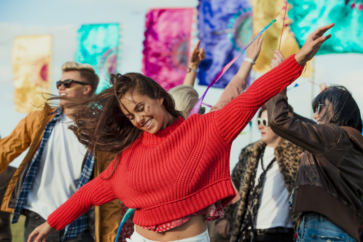 Group of friends dancing and having fun at a music festival.