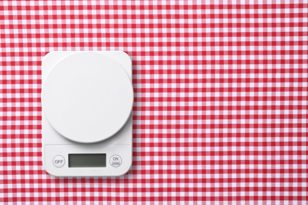 Overhead shot of kitchen digital food weight scale on red gingham check tablecloth.