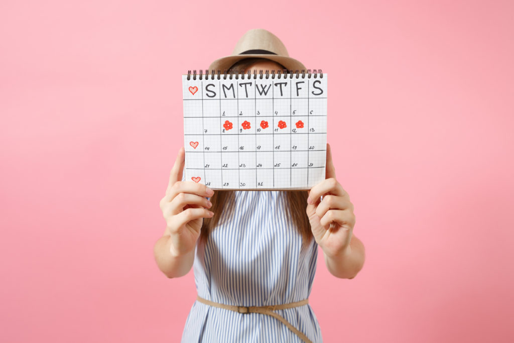 Portrait of woman in blue dress cover face, hiding behind periods calendar for checking menstruation days isolated on trending pink background. Medical, healthcare, gynecological concept. Copy space
