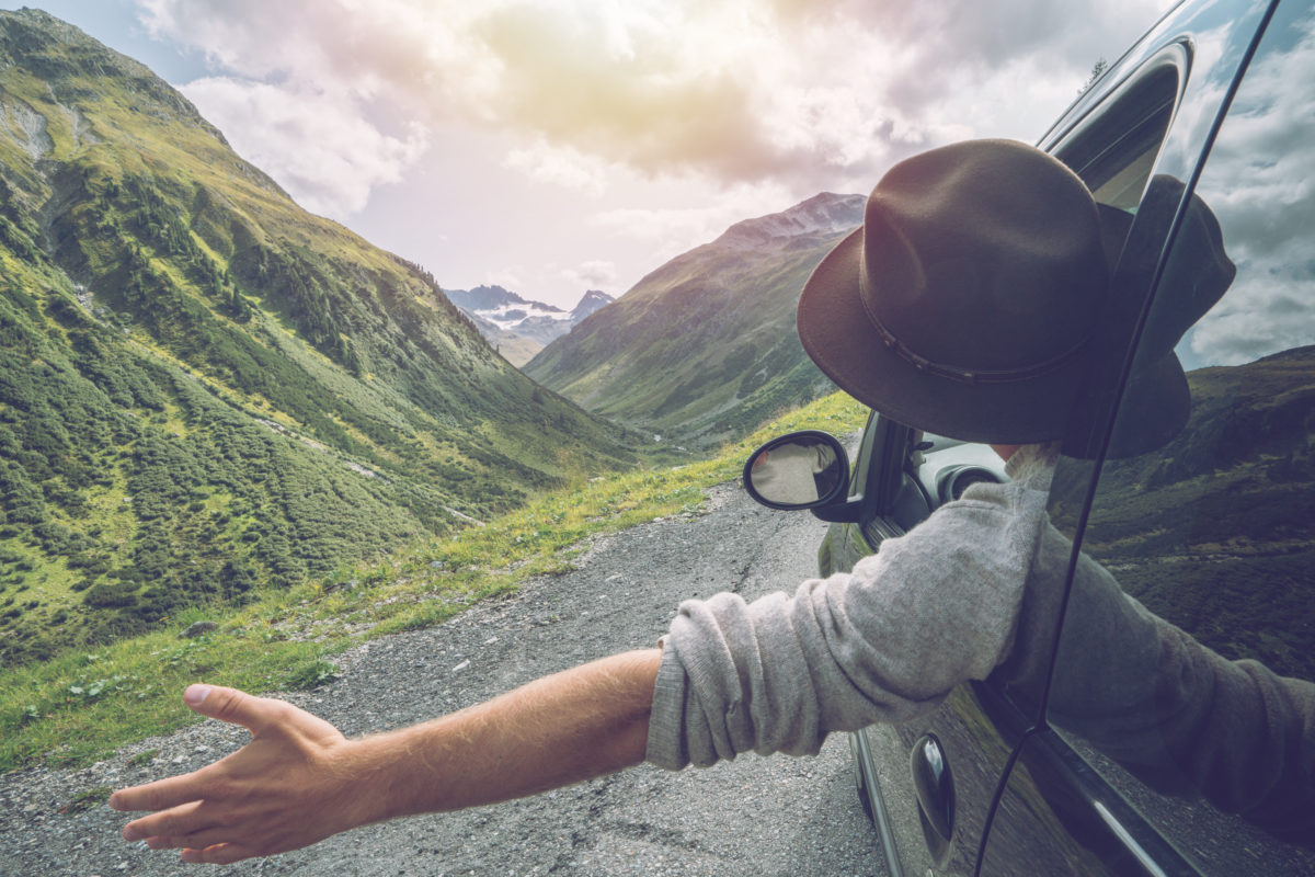 Young man in car on mountain road looks out from window car, outstretched arms for freedom. Mountain landscape in Summer, shot in Graubunden Canton, Switzerland.
