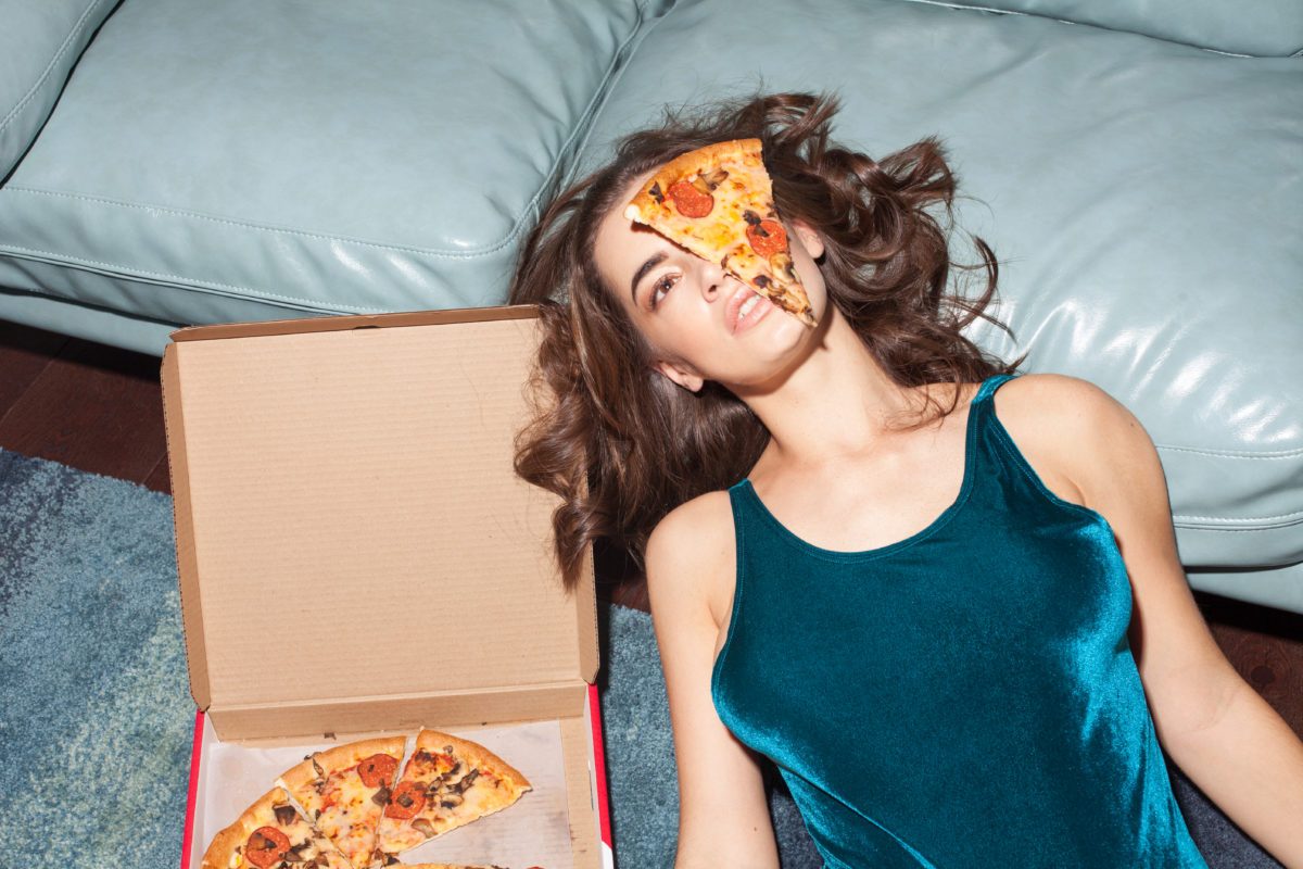 sexy woman lies with pizza on her face indoor, home interior