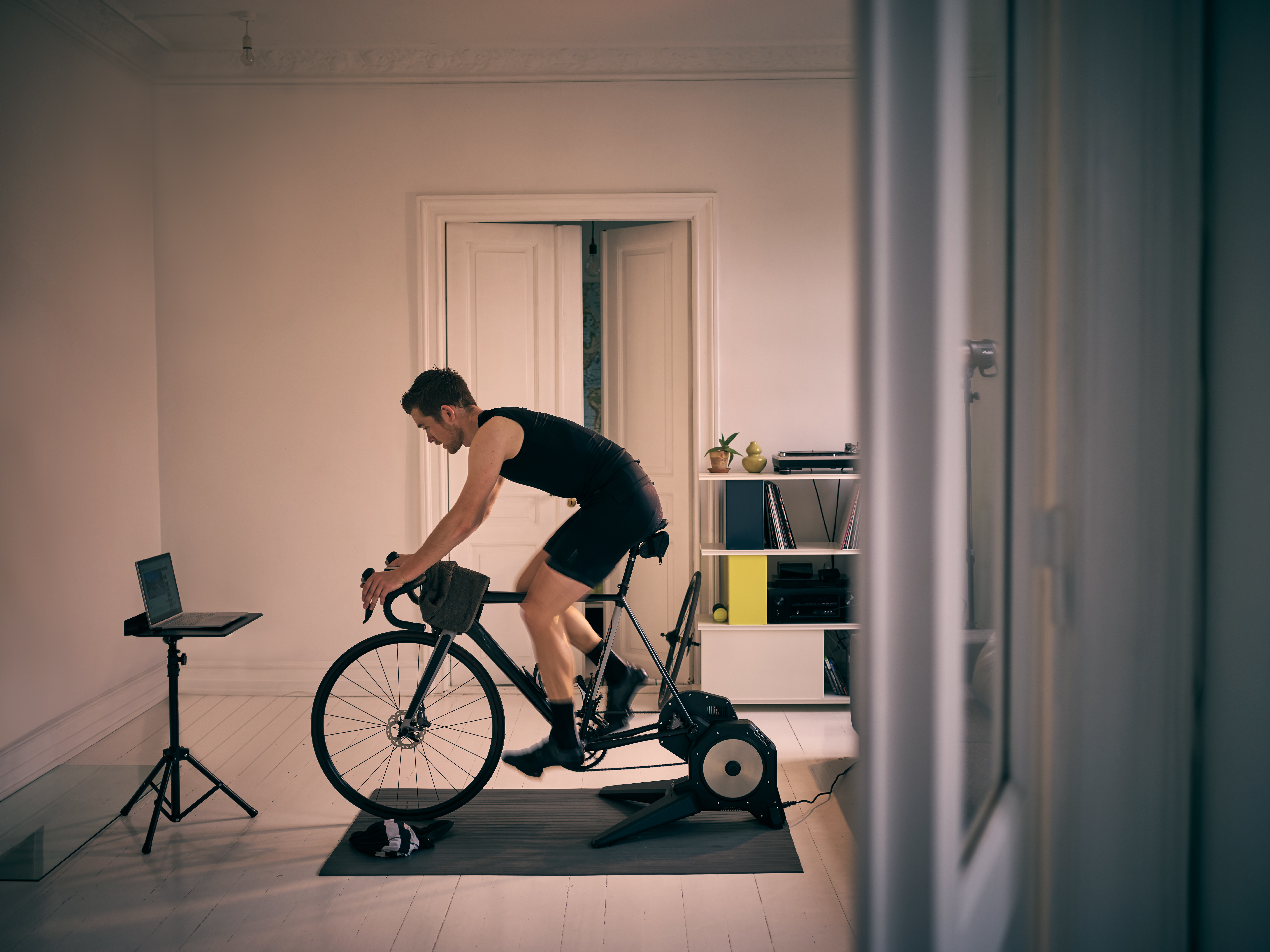 Shot of a young man working out on an exercise bike at home